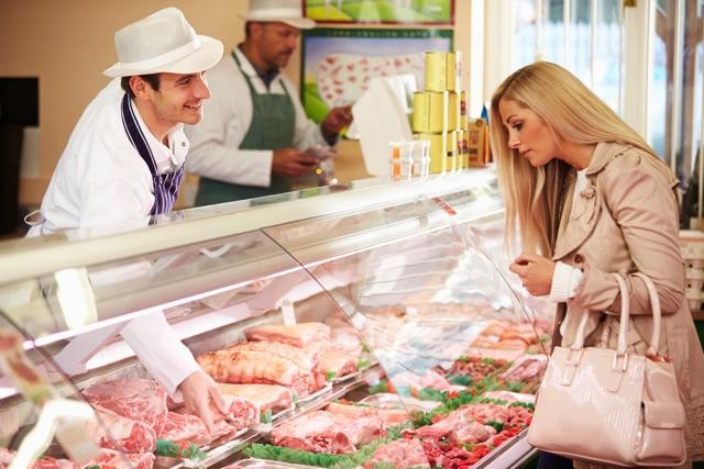 お肉屋さんで品を選ぶ女性