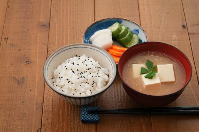 お皿にのったきゅうりと人参と大根のぬか漬けの茶碗に入ったご飯とお椀に入った豆腐の味噌汁