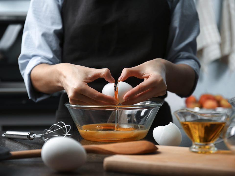 透明のボウルに卵割り入れる