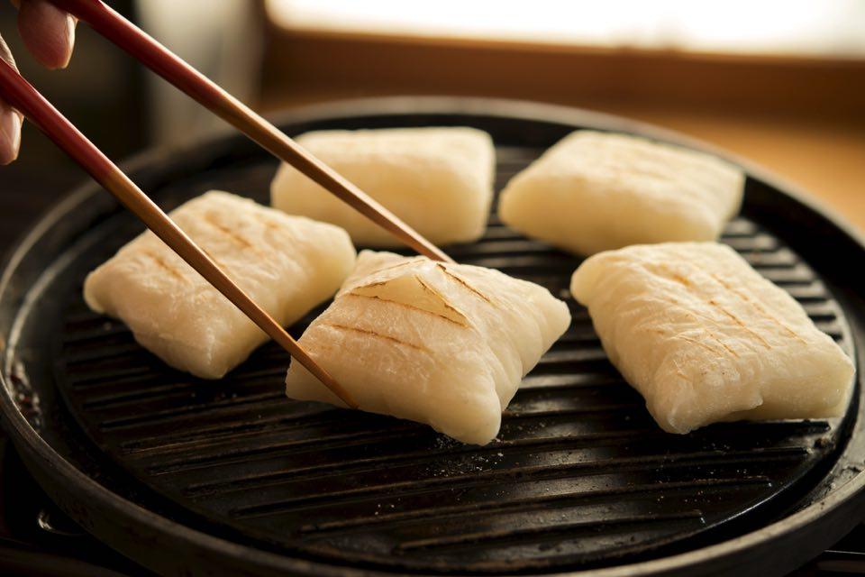 黒い鉄鍋で切り餅を焼いている