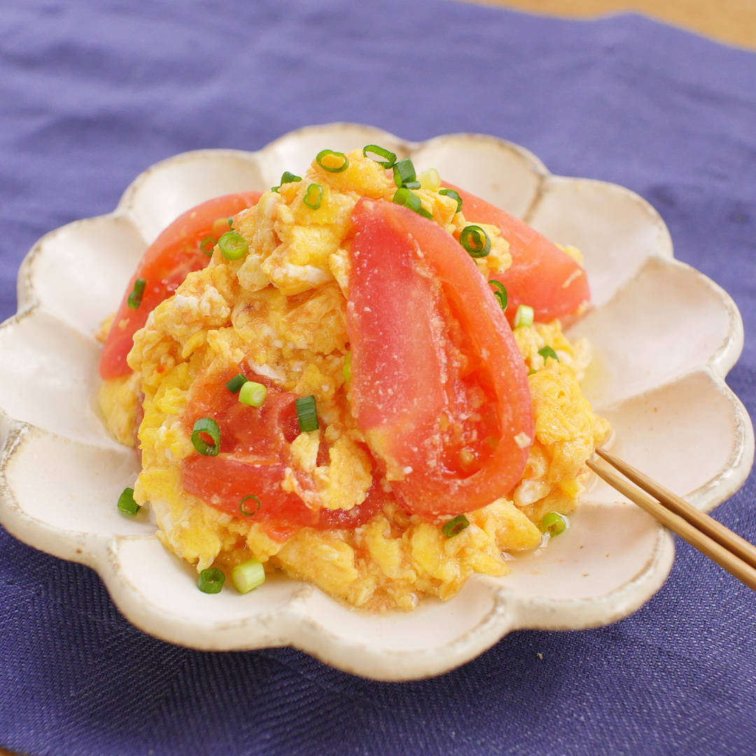 Stir-fried fluffy eggs and tomatoes on a white flower-shaped plate